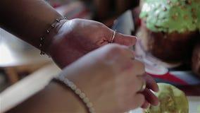 De kok houdt een snoepje in zijn hand bestrooit en haar Pasen-snoepje behandelt verfraait Voorbereiding van Pasen-cakes stock footage