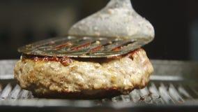 De kok keert een biefstuk op een grill om stock video