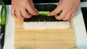 De kok keert nori met rijst om om het vullen uit te spreiden stock video