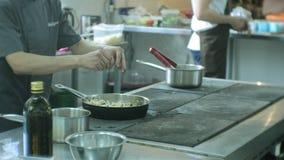 De kok in de keuken van het restaurant bereidt deegwarencarbonara voor stock videobeelden