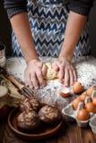 De kok kneedt het deeg op de lijst dichtbij cupcakes en de eieren royalty-vrije stock foto