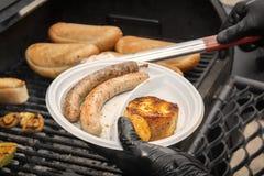 De kok legt geroosterde worsten op houtskoolschotel Straatvoedsel royalty-vrije stock afbeelding