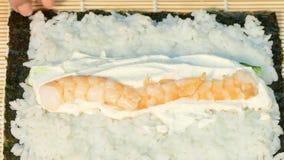De kok legt op de garnalenkaas en rolt het sushibroodje stock videobeelden