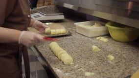 De kok maakt broodje van deeg met gestremde melk het vullen, snijdt in vlakke stukken stock videobeelden