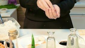 De kok maakt een bal van rijst met zijn handen stock footage