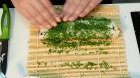 De kok maakt een groene sushi rollen stock video