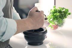 De kok maalt in een steenmortier de ingrediënten stock foto