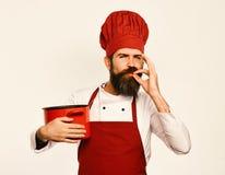 De kok met tevreden gezicht in eenvormig Bourgondië heeft braadpan stock afbeeldingen