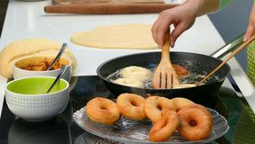 De kok ontwikkelt het deeg en het gebraden gerecht donuts stock footage