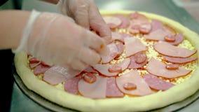 De kok plaatst bacon en gerookte worst op ruwe pizza stock videobeelden