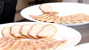 De kok schikt plakken van gebakken vlees en rollade van kip op platen stock videobeelden