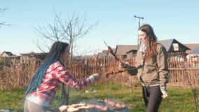 De kok shashlik vlees van twee vrouwenvrienden bovenop houtskoolgrill op binnenplaats Samen het spreken en het glimlachen, hebben stock video