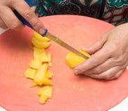 De kok snijdt aardappels op de raad stock foto