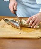 De kok snijdt de gebakken vissen een volledige inzameling van voedselrecepten Royalty-vrije Stock Foto