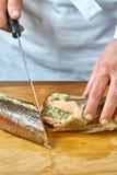 De kok snijdt de gebakken vissen een volledige inzameling van voedselrecepten Royalty-vrije Stock Foto's