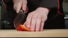 De kok snijdt een groene paprika op een scherpe raad in een keuken stock video