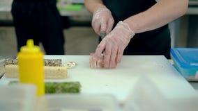 De kok snijdt een Japans broodje met bacon stock video
