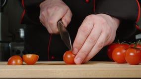 De kok snijdt een kersentomaten op een scherpe raad in een keuken stock video