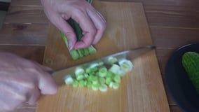 De kok snijdt groene uien op een scherpe raad, sluit karbonade omhoog groene uien stock videobeelden