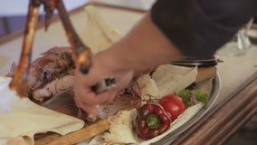 De kok snijdt het karkas van een schaap met brand met een mes wordt geroosterd dat stock videobeelden