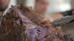 De kok snijdt het karkas van een schaap met brand met een mes wordt geroosterd dat stock video