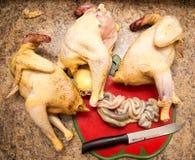 De kok snijdt de kip met een mes stock foto