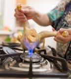 De kok snijdt de kip op brand stock fotografie