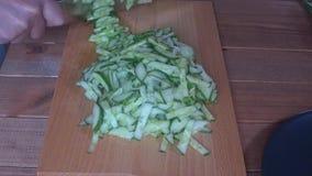 De kok snijdt komkommers op een scherpe raad stock footage