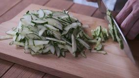 De kok snijdt komkommers op een scherpe raad stock video