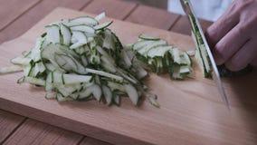 De kok snijdt komkommers op een scherpe raad stock videobeelden