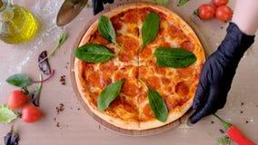 De kok snijdt pizzasalami met spinaziebladeren op plakken, indient rubberhandschoenen, zijaanzicht stock video