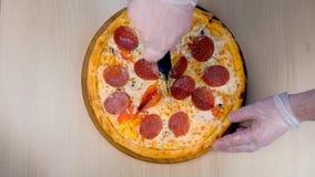 De kok snijdt salamipizza op plakken dient de rubber hoogste mening van het handschoenenclose-up in stock video
