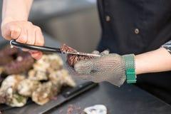 De kok snijdt de zee?gel Het close-up van de oesterhandschoen stock foto's