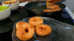 De kok trekt donuts uit de pan stock videobeelden