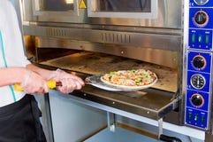 De kok trekt een klaar pizza van de oven terug stock foto