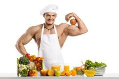 De kok van de mensenbodybuilder met appel op bicepsen Stock Afbeelding