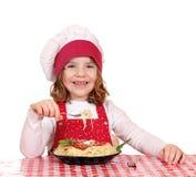 De kok van het meisje eet spaghetti Royalty-vrije Stock Afbeeldingen