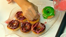 De kok verfraait chocolade donuts stock videobeelden