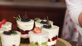 De kok verfraait desserts in glazen, door aardbei, chokeberry slagroom, stock footage