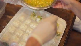 De kok voegt aan het dessert met roomjam toe van kiwi, sinaasappelen en ander fruit in individuele containers voor catering stock footage