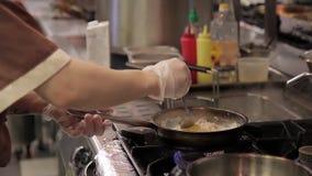De kok voegt een ruw ei aan een hete pan op een gasfornuis toe stock footage