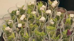 De kok voegt kubussen van feta-kaas in containers met sla op catering toe stock video