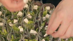 De kok voegt kubussen van feta-kaas in containers met sla op de catering toe stock video