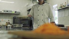 De kok werpt op het voedsel in de pan in langzame motie stock video
