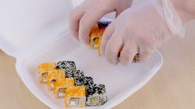 De kok zet broodjes op plastic doos voor levering in restaurant Het proces van spijkers stock videobeelden