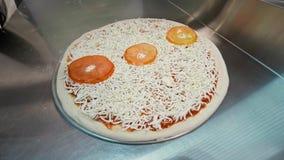 De kok zet tomaten op pizza stock footage