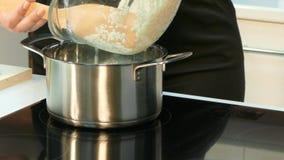 De kok zette de pot op het fornuis en vult het met rijst stock videobeelden