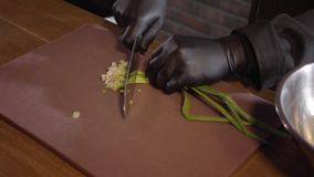 De kok in zwarte rubberchef-kok gloves besnoeiingen verse uien op een scherpe raad in een restaurantkeuken Het concept het koken stock footage