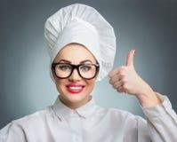 De kokchef-kok van de glimlachvrouw het tonen beduimelt omhoog Royalty-vrije Stock Afbeeldingen