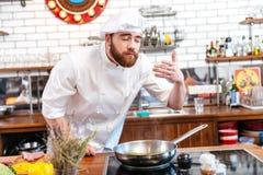 De kokende en ruikende aroma's van de gelukkige geïnspireerde chef-kokkok van voedsel Royalty-vrije Stock Foto's
